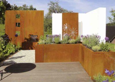 Passt – Geschlungene Gestaltung aus Pflanzen, Cortenstahl und Putzmauer